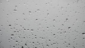 Rain drops falls on a window on a stormy day stock footage