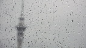 Rain drops falls on a window on a stormy day while sky tower auckland new zealand in the background. Rain drops falls on a window on a stormy day while sky tower stock video