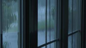 Rain drops flowing down window glass. Rain water hitting house windows during thunderstorm stock video