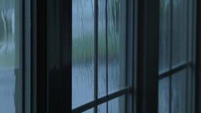 Rain drops flowing down window glass. Rain water hitting house windows during thunderstorm stock video footage