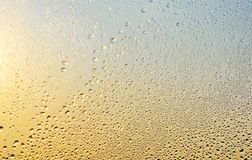 Rain drops and frozen water on window glass background. Golden and silver colors Royalty Free Stock Photos