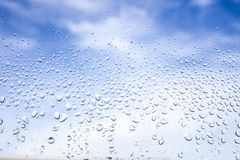 Rain drops on the glass. In the background blurred blue cloudy sky. After raining concept Stock Photos