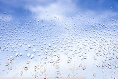 Rain drops on the glass. In the background blurred blue cloudy sky. After raining concept Royalty Free Stock Image