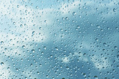 Rain drops on glass. Blue rain drops on glass Stock Photo