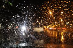 Rain drops on glass of car window with street bokeh at night in rainy season. White light from motorcycle And yellow from the car On the night of heavy rain in royalty free stock images