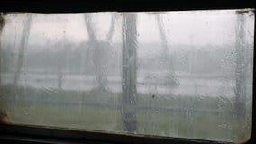 Rain drops on the glass. Condensation of water drops on the glass. Water drops falling on glass. Rain running down on train window. Rainy season stock video footage
