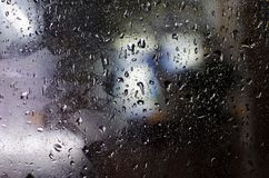 Rain drops on the glass in the dark. Of the light in the background Stock Photos