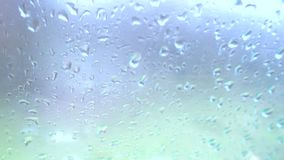 Rain drops on glass. Rain falling on glass during rain storm, close up stock video footage