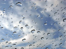 Rain drops on glass and sky. Rain drops on window with cloudy blue sky in the background Stock Photos