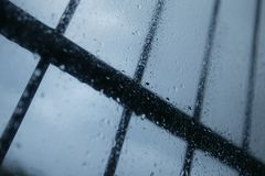 RAIN DROPS ON GLASS WINDOW PANE. WITH SECURITY BARS Stock Photography