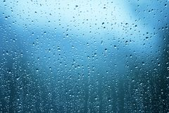 Rain drops on the glass window. As background. Blue color tone used royalty free stock image