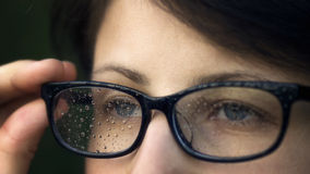Rain drops on the glasses 2. Girl with a vision problem, looks through the glasses. Glasses covered with drops of water (rain Royalty Free Stock Photography