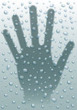 Rain drops hand. Hand behind a glass with raindrops Stock Image