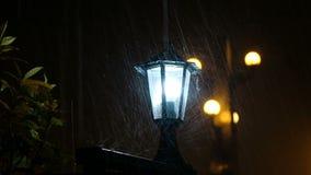 Rain drops hit the street lamp, the light illuminates the water close-up stock video