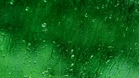 Rain drops motion water green glass background stock footage