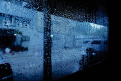 Rain drops pouring down on window glass Stock Images
