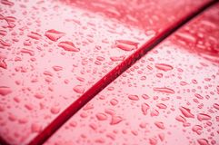 Rain drops on red car royalty free stock image