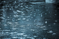 Rain drops. Rippling in a puddle with blue sky reflection Stock Photo