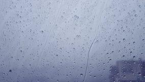 Rain drops running down on a window pane. Blue tint. stock video footage