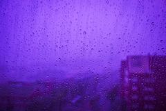 Rain drops running down on a window pane. Storm Rain drops running down on a window pane during a storm. 18-3838 Ultra Violet pantone style Stock Photo
