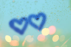 Rain drops and two hearts write on window with light bokeh. Royalty Free Stock Photo