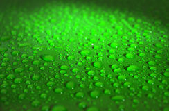 Rain drops on the vaxed hood of the green car Stock Image