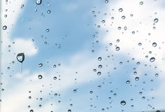 Rain drops, water drops of rain on a window glass with blurred sky clouds Royalty Free Stock Image