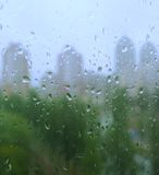 Rain drops on a window. And mystic silhouette of city Royalty Free Stock Image