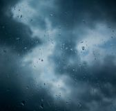 Rain drops on window across clouds Stock Images