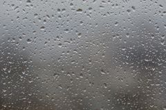 Rain drops on window,. Against blurry background of a town Royalty Free Stock Photography