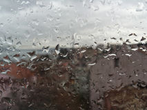 Rain drops on window against buildings Royalty Free Stock Photos