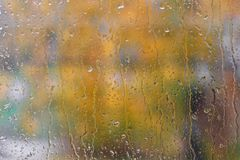Rain drops on the window on the background of autumn blurred the landscape. The weather typical of autumn Royalty Free Stock Photo