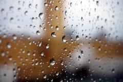 Rain drops on window, balcony in background Stock Photos