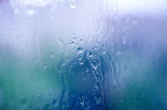 Rain drops. On a window with a blurred colorful background Stock Photo