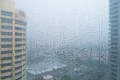 Rain drops in window with cityscape Stock Images