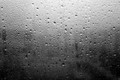 Rain drops on window close-up in black and white. Abstract seasonal background and texture Royalty Free Stock Photos