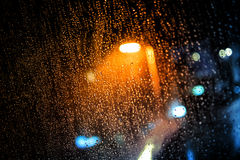 Rain drops on the window with dark streets outside Stock Photography