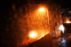 Rain drops on the window with dark streets outside Stock Photo