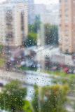 Rain drops on window glass and blurred street Stock Image