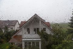 Rain drops on window glass with view to the neighbor house Stock Images