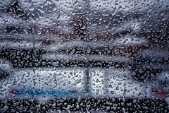 Rain drops on window glass surface with cloudy background stock photo