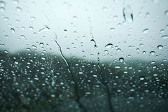 Rain drops on window glasses surface with cloudy background . Rain drops on window glasses surface with cloudy background Stock Photos