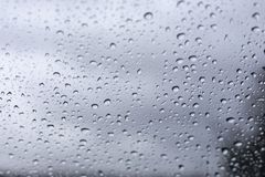 Rain drops on window glasses surface with cloudy background . Natural Pattern of raindrops isolated on cloudy background royalty free stock photo