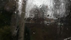 Rain Drops on the window of a moving train in spring with trees, bushes and houses passing by stock video