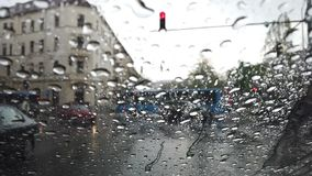 Rain drops on a window overlooking a road with passing cars stock video footage