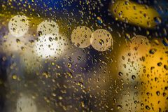 Rain drops on window. Peaceful evening or night at home when raining outside. Water drops on glass. Surface of wet glass. Water splash. City lights bokeh stock photos
