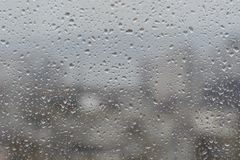 Rain drops on window,. Against blurry background of a town Royalty Free Stock Image
