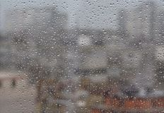 Rain drops on window,. Againt blurry background of a town Stock Photography