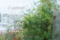 Rain drops on window and romantic text `Iwant to kiss you in the rain...` royalty free stock image