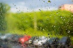 Rain drops on the window. A row of blurry cars outside the window. Summer rain on a sunny day. Stock Photos